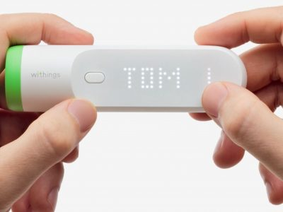 two hands holding a withings smart thermometer