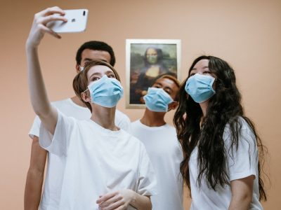 group of people taking a selfie in face masks