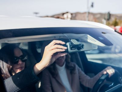 two women in car adjusting dash cam